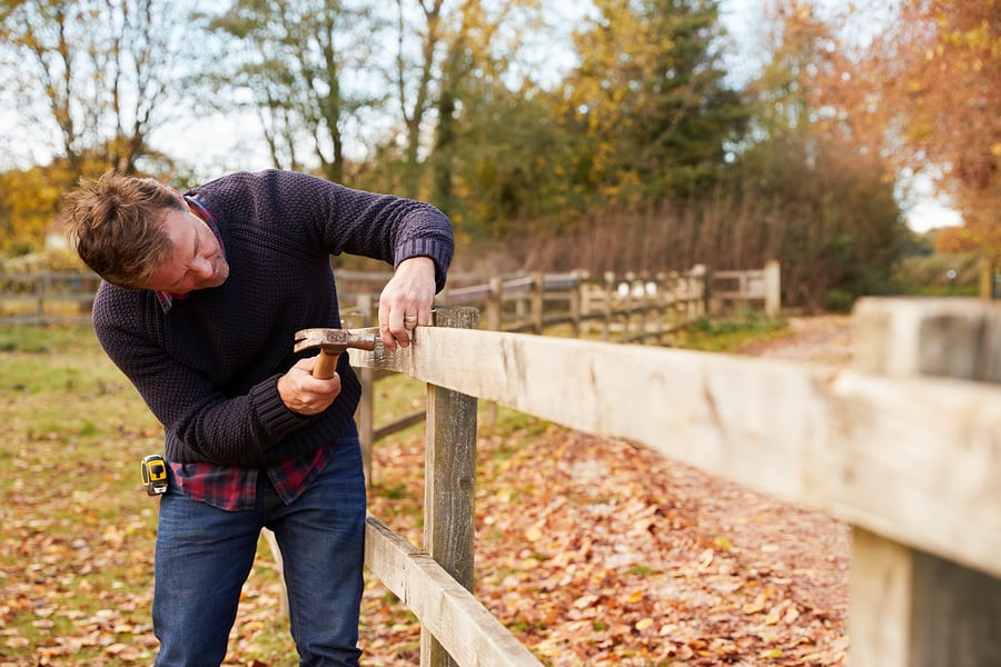 Mature Man Hammering Nail Into Repaired Fence | About our Fence Builders